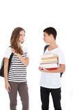 Two Teenagers on White Background Talking. Teenage boy and girl with school supplies talking isolated on white in studio Royalty Free Stock Photography