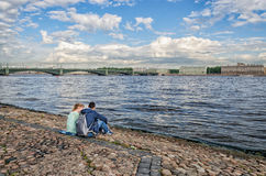 Two teenages sitting by the walls of Peter and Paul fortress. Stock Image