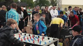Two teens absorbedly play american table soccer among other. Summer festival. Sand. People stock video footage