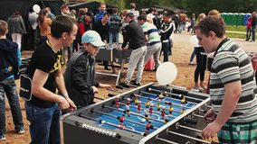 Two teens and adult men absorbedly play american table soccer. Summer festival. Sand. People stock video
