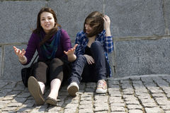 Two teens friends sitting on stone Royalty Free Stock Photo