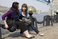 Two teens girl sitting on embankment. Stock Photos