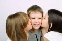 Two teens girls kissing little laughing boy. On thr light background horizontal Stock Photo