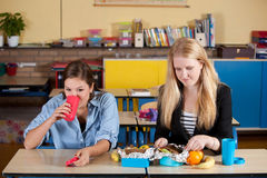 Two teens having a healthy lunch. Two teenagers having a healthy school lunch in the classroom Royalty Free Stock Photos