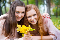 Two teens holding yellow leaves Stock Photography