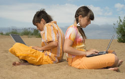Two teens  with laptops Royalty Free Stock Photo
