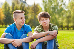 Two teens sitting together on green meadow Stock Images