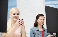 Two teens with smartphones in computer class Royalty Free Stock Images