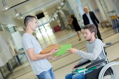 Two teens standing in university corridor one disabled Royalty Free Stock Photos