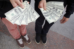 Two teens staying with funs of dollars in hands Stock Photography