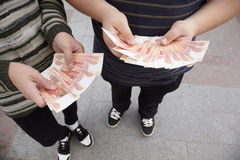Two teens staying with funs of russian roubles Stock Images