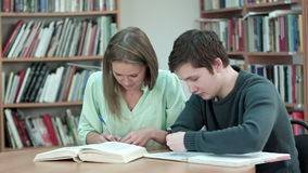 Two teens studying at library. Professional shot in 4K resolution. 075. You can use it e.g. in your commercial video, business, presentation, broadcast video stock video