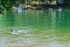 Two teens swimming in the lake royalty free stock photo
