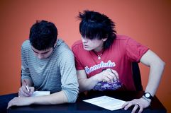 Two Teens Taking Exam. Two male teens site side by side.  One is working on his paperwork and the other is leaning in towards him to look at his work Royalty Free Stock Photo