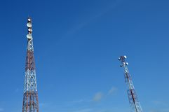 Two telecommunications tower. Against blue sky Stock Photos