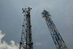 Two telecommunications towers against the sky. Cloundy Royalty Free Stock Photography