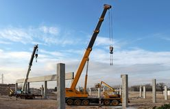 Two telescopic cranes and cherry picker among the supporting columns of the new building to be built. Building activity stock image