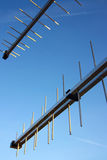 Two television antennas under blue sky. Two television antennas under clear blue sky Stock Photos