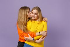 Two tender cute young blonde twins sisters girls in vivid colorful clothes hugging kissing on cheek  on pastel stock images