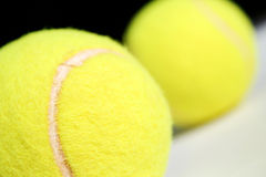 Two tennis balls. Two yellow tennis balls on a black and white background Stock Photos