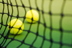 Two tennis balls in green court, black weaved net as forground Royalty Free Stock Photography