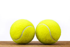 Two tennis balls table wood isolated Royalty Free Stock Photography