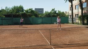 Two tennis girls players playing double at tennis court. Two tennis players playing double at tennis court stock video