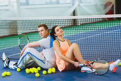 Two tennis player relaxing next to a net.  Royalty Free Stock Image