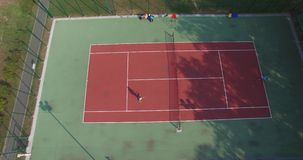 Two tennis players on the court.  Long rally. Aerial view. Two men playing tennis on the hard court stock video footage