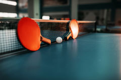 Two tennis rackets and ball against net on table Stock Image