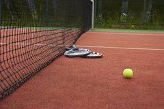 Two tennis rackets and ball on court. Two tennis rackets and ball lying on a red tennis court Royalty Free Stock Images