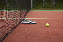 Two tennis rackets and ball on a tennis court. Two tennis rackets and ball lying on a red tennis court Royalty Free Stock Photos