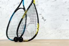 Two tennis rackets and balls standing by the wall Royalty Free Stock Photography