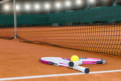 Two tennis rackets with a tennis ball lying near net on clay cou Royalty Free Stock Photography