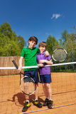Two tennis winners standing next to the net Royalty Free Stock Photos