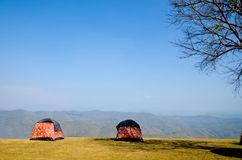 Two tents camping beside the cliff sky background. royalty free stock photography