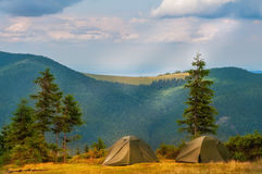 Two tents in a clearing in the mountains. Two tents in a clearing near large fir trees. In the background is a beautiful view of the green mountains covered Stock Photography