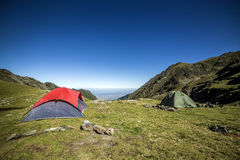 Two tents  in the mountains under the blue sky. In summer Stock Image