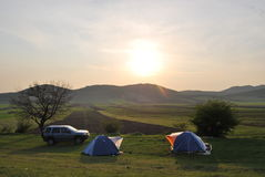 Camping in the wilderness. Two tents and an offroad car in the wild and a beautiful sunset Stock Photo