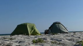 Two tents are on a sandy beach of the Black Sea at sunset. An impressive view of two tents placed on a sandy beach of the Black Sea at sunset in summer. Their stock footage