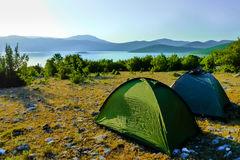 Two tents during sunrise on the rocky ground. Two tents set up on a rocky ground near the lake in Bosnia and Herzegovina. Sunrise around 5 am. An overnight stop Stock Images