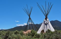 Tepees in the landscape. Two tepees, one without skin, showing the poles stock photos
