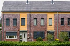 Two terraced houses decorated with diverse plants, modern dutch architecture, village homes in the Netherlands. Two terraced houses decorated with diverse plants stock photography