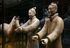 Two terracotta soldier and hor. Two terracotta statues of the Chinese soldiers stand near to a horse Royalty Free Stock Images