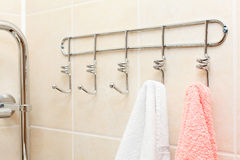 Two terry towels hanging on a hooks stock photos