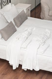 Two terry white bathrobe on bed Royalty Free Stock Images