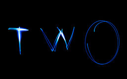 Two - text. Painting light luminescent inscription word Royalty Free Stock Photography