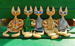 Two textile toy cats with big expressive eyes are sitting on a green bench on a sunny summer day and holding their paws. Beautiful dresses, hand-sewn. Fabric royalty free stock image
