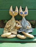 Two textile toy cats with big expressive eyes are sitting on a green bench on a sunny summer day. Two stitched textile toy cats with big expressive eyes are stock photography