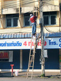 Two Thai electricians are fixing confusing electricity lines on a pole. Stock Photo